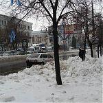 21 декабря 2009 в Луганске. Кто-то вешает голубые ленточки, а автолюбитель чистит снег.